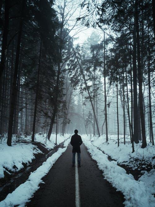 man standing in snowy woods