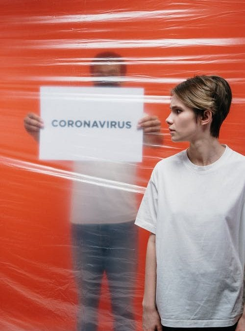 woman with sign saying coronavirus in background